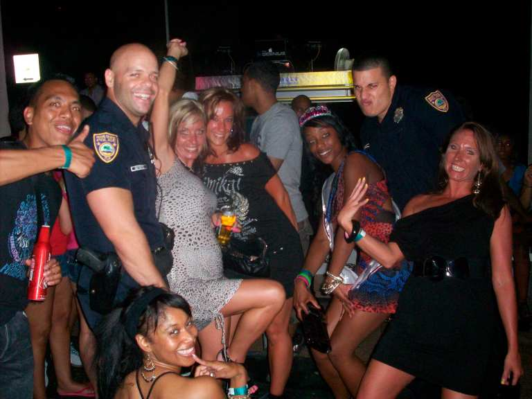 Handout photo of Miami Beach police officers posing with a group of women in Miami Beach